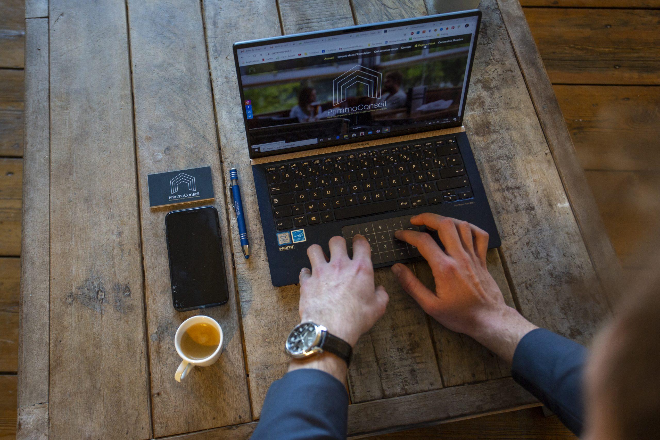 primmo conseil goddard photo mains tapant sur clavier ordinateur portable posé sur table en bois
